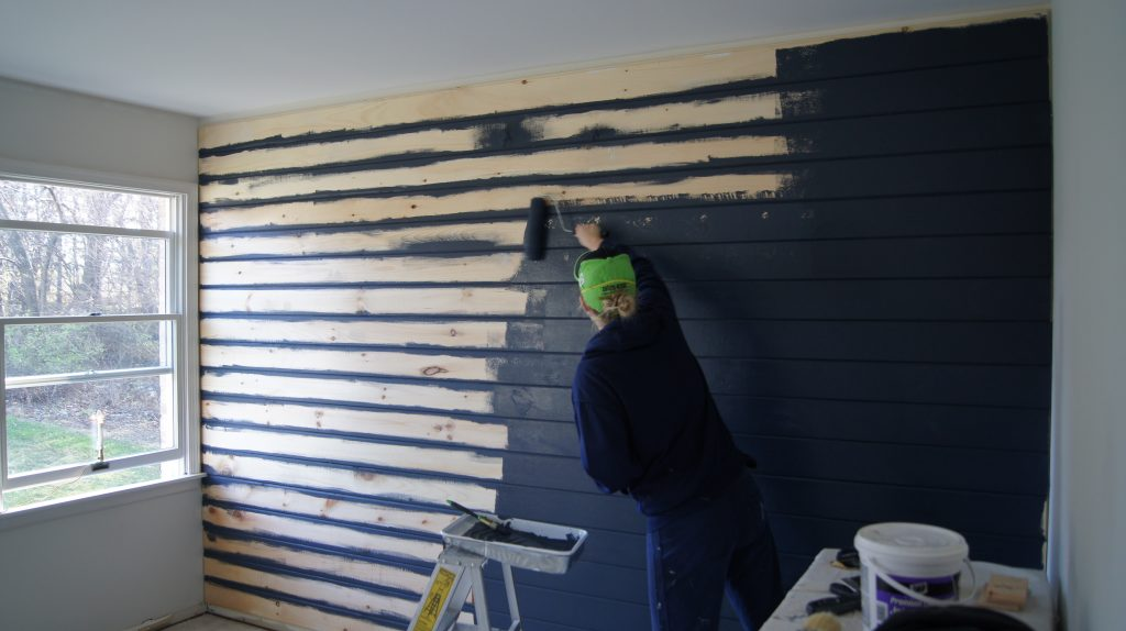Rolling navy blue paint on tongue and groove boards installed on wall